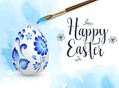 Hand painted Easter egg and paintbrush on a blue watercolor background. Russian folk painting art style Gzhel. Vector illustration. Happy Easter lettering