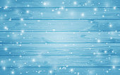 Blue snow-covered wooden background. Winter. Snowstorm. Snowfall. Christmas wood background. Night and snowflakes on the background of boards.