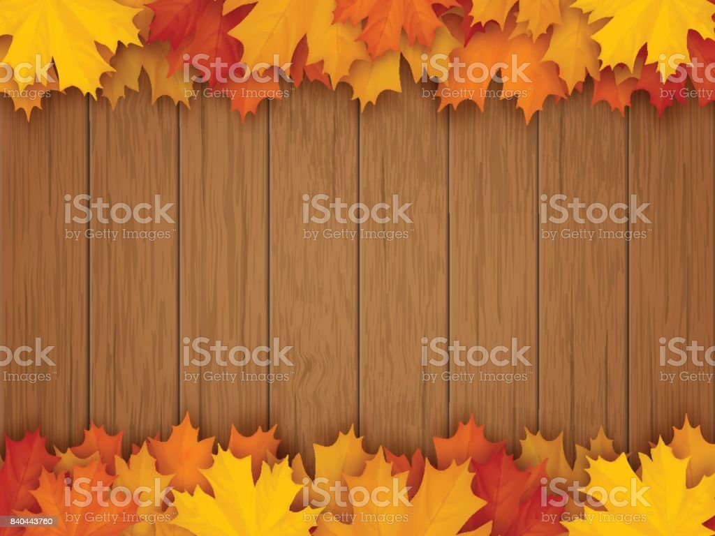 Border from fallen maple leaves on wooden background
