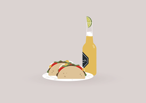 A bottle of cold light beer with a slice of lime inside and two tacos on a plate, a traditional Mexican street food with meat and vegetables