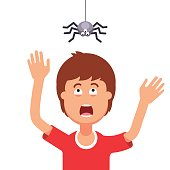 Boy afraid of a spider hanging from the top