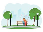 Boy and girl hugging sitting on a Park bench.