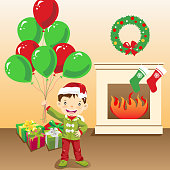 Little boy holding balloons in front of mantelpiece in Christmas.