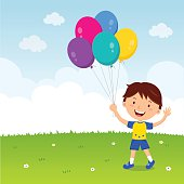 Happy boy gesturing with colorful balloons.