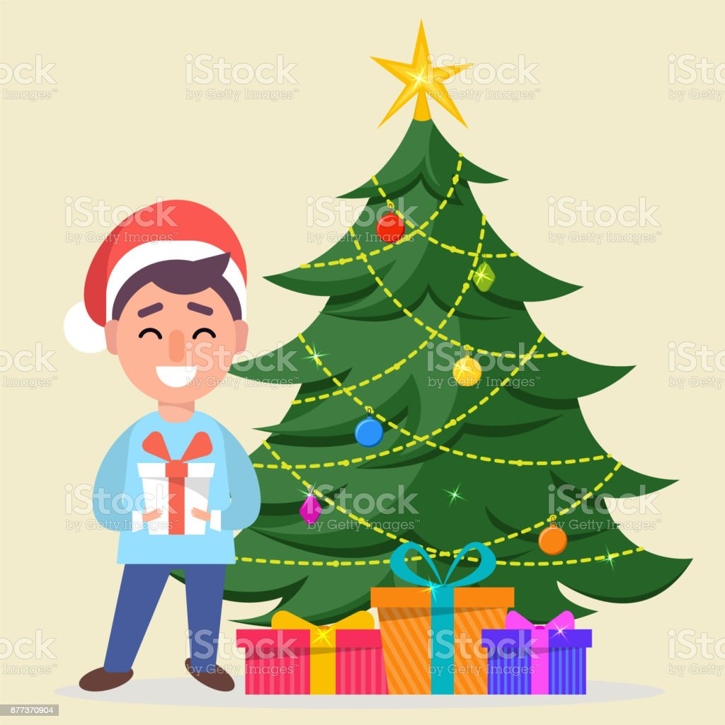 boy in santa claus hat standing near decorated christmas tree with gift boxes under it royalty