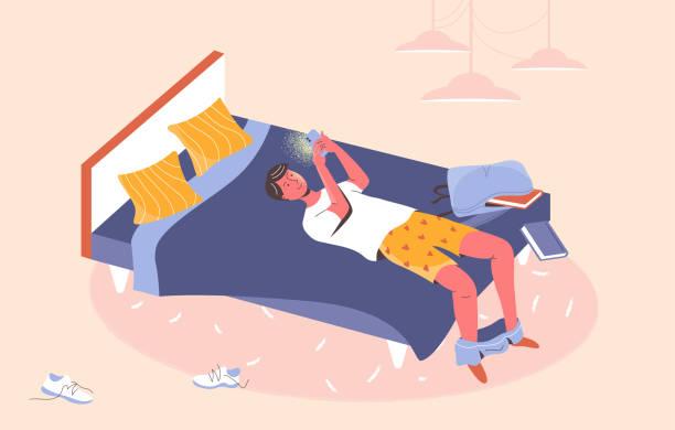 スマートフォンのチャット、ゲーム、ソーシャルネットワークで先延ばしに部分的に服を脱いでベッドに横たわっている少年。携帯電話の依存。covid-19ロックダウン中のモバイル通信に夢中� - スマホ ベッド点のイラスト素材/クリップアート素材/マンガ素材/アイコン素材