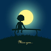 Boy sitting lonely in the moonlight