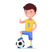 Boy soccer player standing with foot on a ball