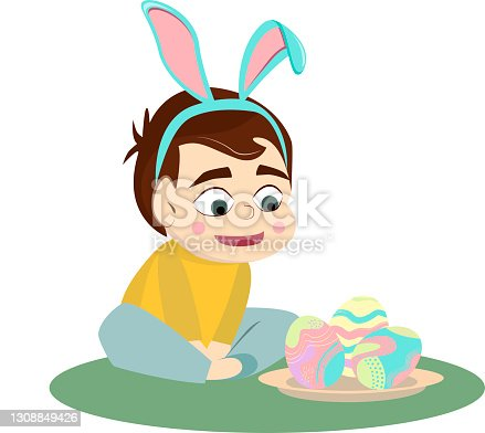 istock boy with bunny ears looks at Easter eggs 1308849426
