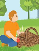 A boy sits next to a picnic basket in a park. he closes the lid after taking an apple out. The background is a green grassy park with trees and a blue sky.