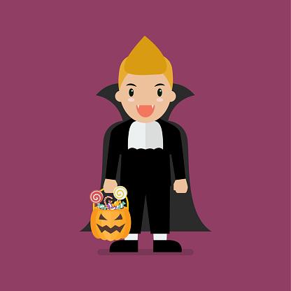 Boy with pumpkin basket dressed in vampire costume