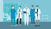 Professional doctors and nurses posing together in a hospital ward and wearing protective suits, virus outbreak emergency concept