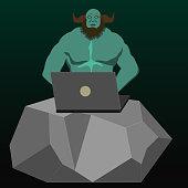 Brawny internet troll, behind the laptop on the big stone