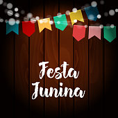 Brazilian Festa Junina greeting card, invitation. Party decoration, string of lights, paper flags, old wooden background. Vector illustration.