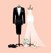 Bride and groom wedding outfits on mannequins, pastel pink background.