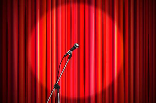 Bright red curtain with shiny microphone in round spotlight lighting, retro theater stage wide background