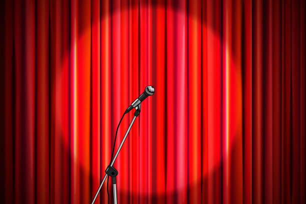 bright red curtain with shiny microphone in round spotlight lighting, retro theater stage wide background - comedian stock illustrations