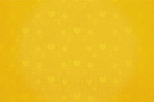 Bright mustard yellow coloured grunge Xmas Background with Christmas ornaments watermark. Slightly lighter tone objects in small size all over the backdrop. Can be used as Valentine's Day, Xmas, New Year, birthday party celebrations wallpaper, background or gift wrapping sheet.