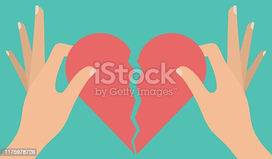 Woman's hand tearing apart a red heart