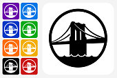Brooklyn Bridge Icon Square Button Set. The icon is in black on a white square with rounded corners. The are eight alternative button options on the left in purple, blue, navy, green, orange, yellow, black and red colors. The icon is in white against these vibrant backgrounds. The illustration is flat and will work well both online and in print.