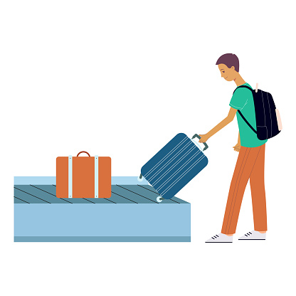 Brunet tourist man picks up his suitcase on wheels from the luggage tape at the airport.
