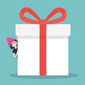 Brunette girl peeping from behind a giant gift box