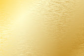 Brushed gold metal plate with light reflections.