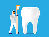 Dental professional in protective gear holds a toothbrush while standing next to a tooth.