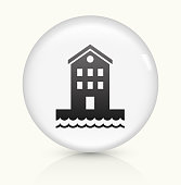 Building near Water Icon on simple white round button. This 100% royalty free vector button is circular in shape and the icon is the primary subject of the composition. There is a slight reflection visible at the bottom.