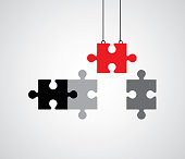 Vector illustration of a red puzzle piece being lowewr into a set of connected puzzle pieces.