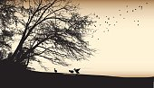 A vector silhouette illustration of an outdoor par scene with ducks along the shoreline of a body of water with a large tree and birds flying above all in a sepia tone.