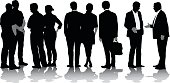 A vector silhouette illustration of a line of business men and woman including a group of four people talking, a couple standing together, a man with a briefcase, and two men going for a hand shake.