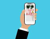Business man holding a smartphone, looking at coronavirus pandemic news vector illustration. Smartphone with coronavirus icon and yellow black warning sign on screen. Blue background.