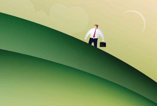 Business man walking up a hill