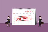 istock Business people look a postponed rubber stamp on a calendar 1264662308