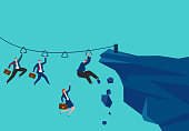 Business people use ropes to slide to another mountain and risk falling off the cliff while sliding