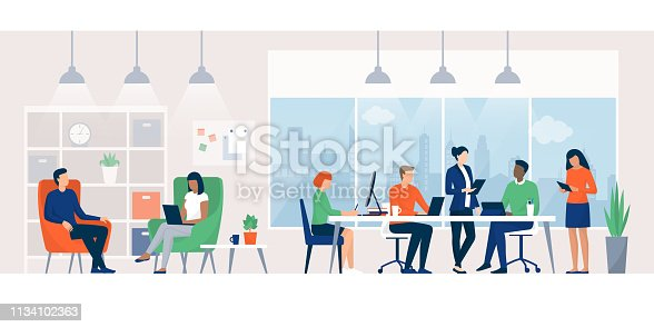 Business people working together in a co-working space, they are connecting with their computers and discussing a project, teamwork concept