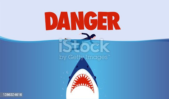 istock Business person in danger - Businesswoman swimming in ocean with big shark threat underneath 1286324616