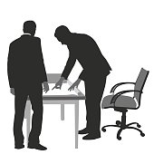 Silhouette vector illustration of two business men looking at a spreadsheet on a desk