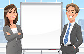 A businessman and a businesswoman giving a presentation at a blank whiteboard, ready for your text, in the office in front of a window. Concept for teamwork, success and presentation techniques.