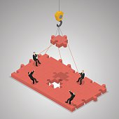 A business team building a puzzle jigsaw. Teamwork business concept. Isometric illustration vector.A business team building a puzzle jigsaw. Teamwork business concept. Isometric illustration vector.