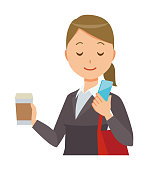 Business woman in suit wears coffee and is manipulating smartphone