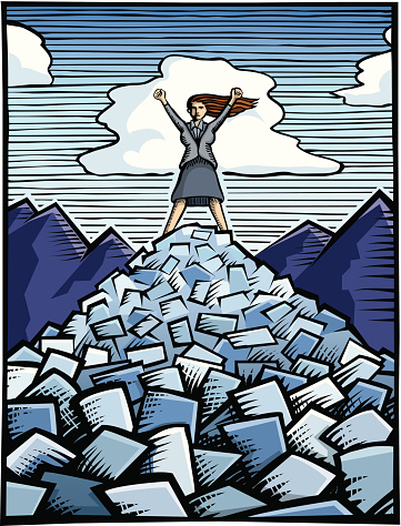 Woman in business suit standing on a pile of paperwork/bills with arms held triumphantly over her head.