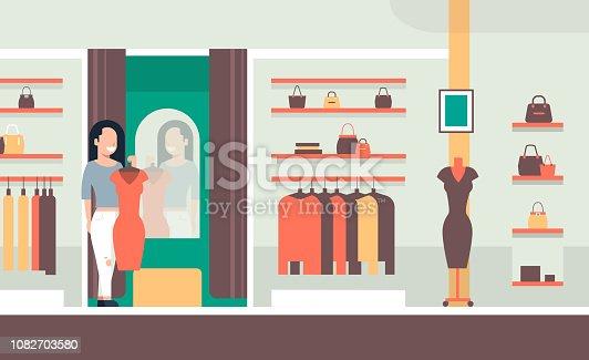 a11597348 1082704886istock mujer de negocios probando nuevo vestido elegante mujer  mirando al espejo moda tienda ropa femenina