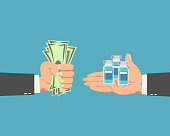 Hand of businessman with money buying the Coronavirus vaccine isolated on blue background.Covid-19 corona virus vaccination with vaccine bottle.