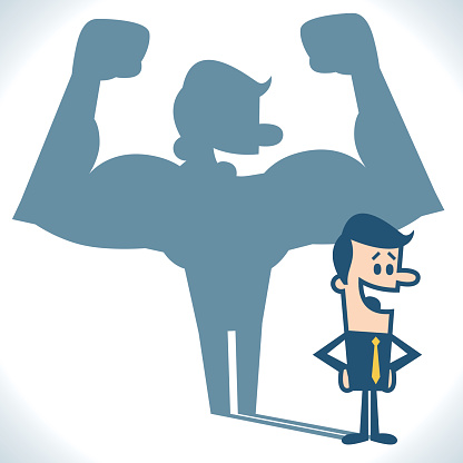 Businessman casting strong man shadow.