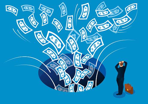 Businessman desperately watching money being sucked into dark hole