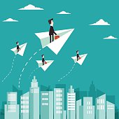 Businessman flying with paper plane over city
