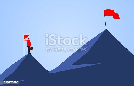 istock Businessman holding a flag standing on the top of the mountain, looking to another higher mountain, business goals and challenges 1226773590