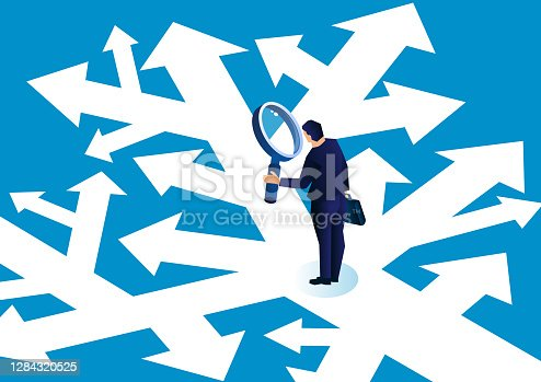 istock Businessman holding a magnifying glass standing in a complicated arrow path observing and making a choice 1284320525